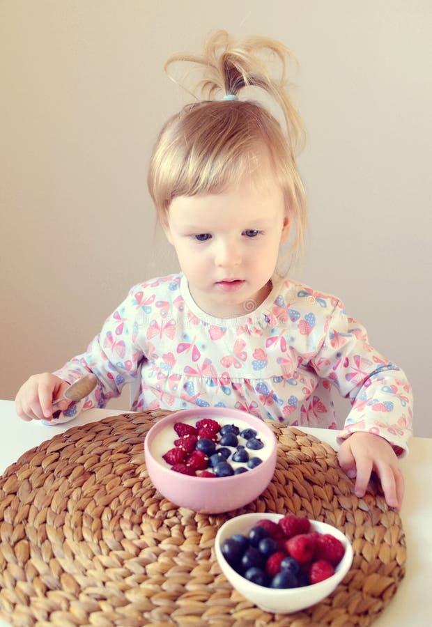 Behandla som ett barn lite flickan som hemma äter den sunda frukosten, bär och yoghurt royaltyfria foton