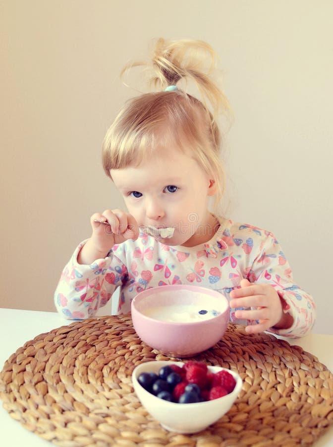 Behandla som ett barn lite flickan som hemma äter den sunda frukosten, bär och yoghurt royaltyfri fotografi