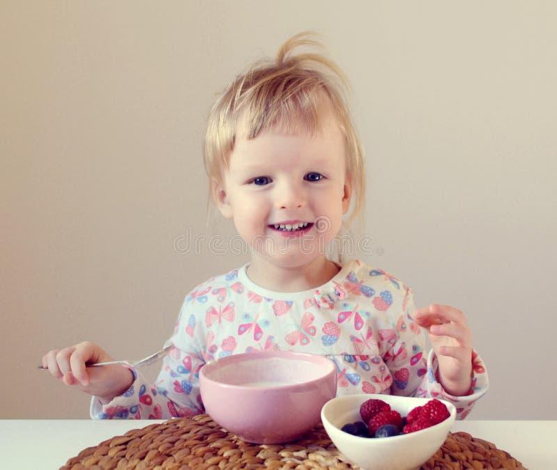 Behandla som ett barn lite flickan som hemma äter den sunda frukosten, bär och yoghurt fotografering för bildbyråer