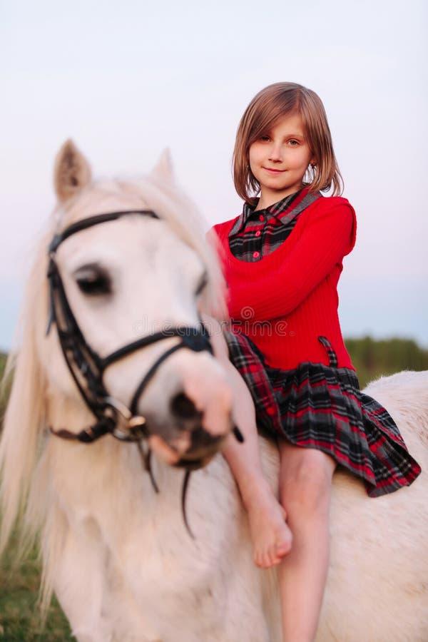 Behandla som ett barn lite flickan i klänningen som från sidan sitter på en vit häst royaltyfri foto