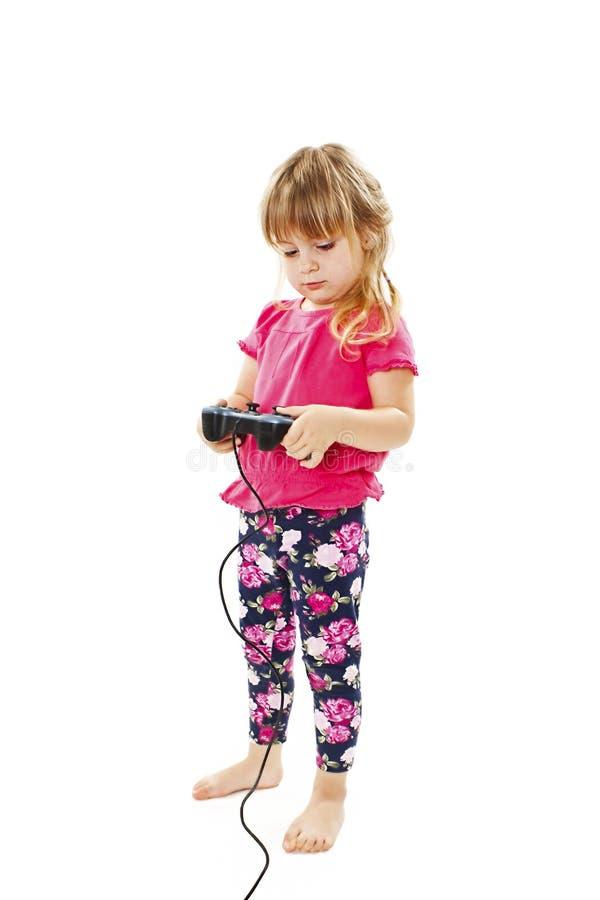 Behandla som ett barn lite flickan som använder videospelkontrollanten arkivfoton