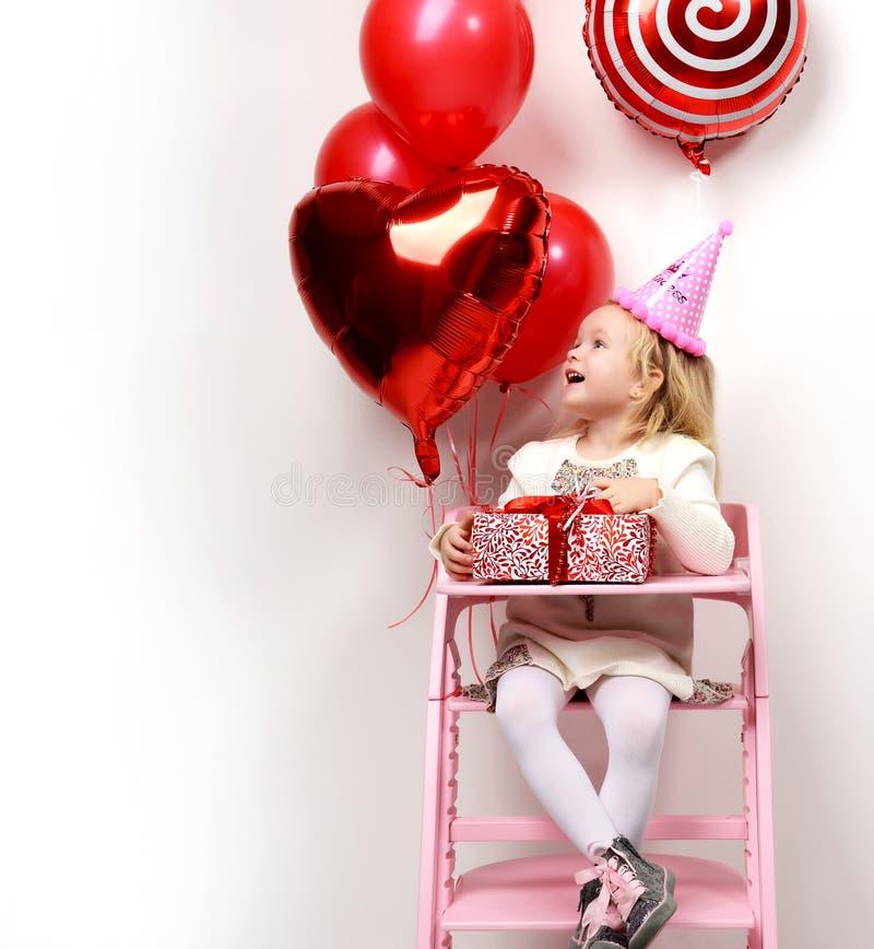 Behandla som ett barn lite flickan som ungen firar hennes födelsedag med den röda närvarande gåvan och ballonger royaltyfria bilder