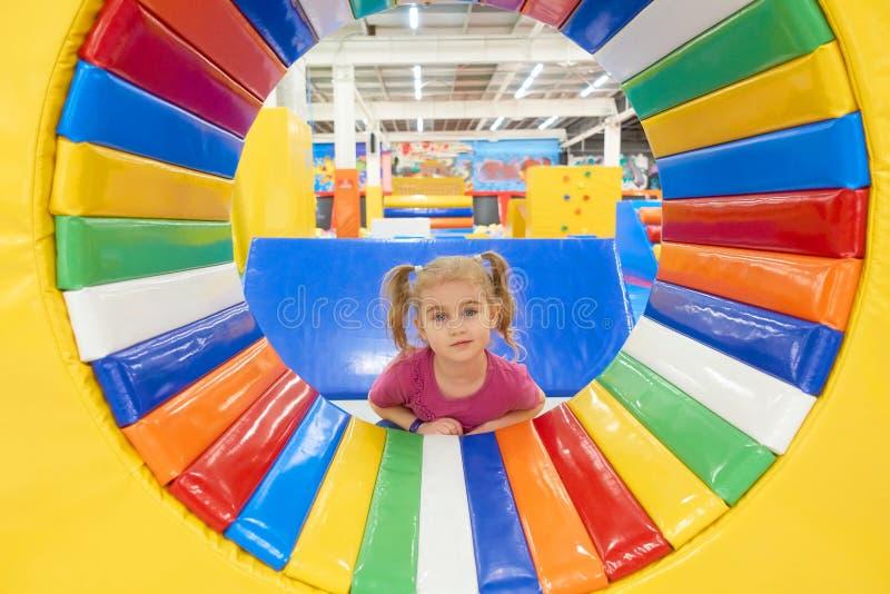 Behandla som ett barn lite gulligt spela i inomhus lekplats arkivbilder