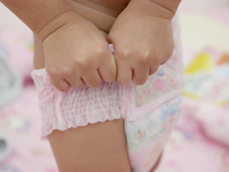 Behandla som ett barn lite händer för ` som s sätter på en blöja vid henne royaltyfri bild