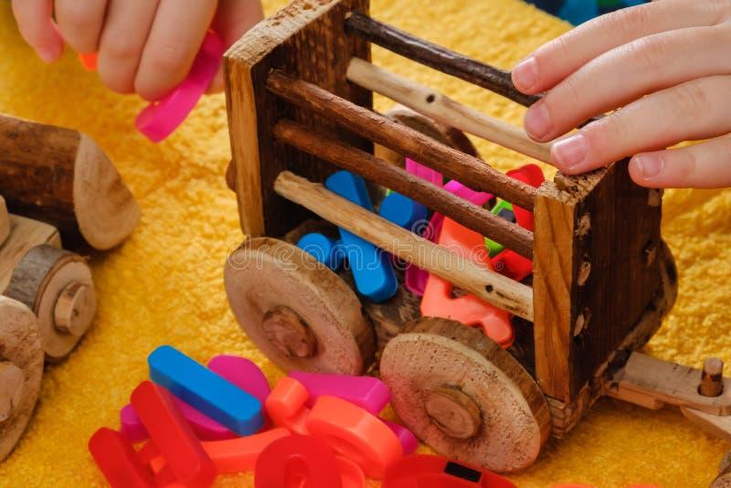 Behandla som ett barn lite handen som spelar med färgrika leksaker och bokstäver royaltyfri foto