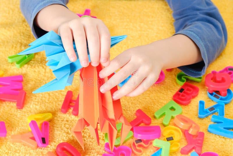 Behandla som ett barn lite handen som spelar med färgrika leksaker och bokstäver royaltyfri bild