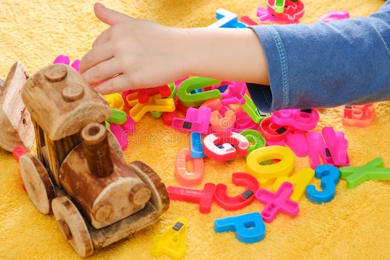Behandla som ett barn lite handen som spelar med färgrika leksaker och bokstäver arkivbilder