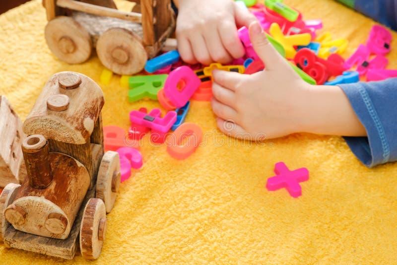 Behandla som ett barn lite handen som spelar med färgrika leksaker och bokstäver arkivfoton