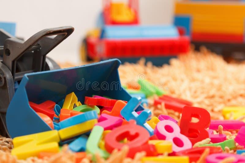 Behandla som ett barn lite handen som spelar med färgrika leksaker och bokstäver royaltyfria foton