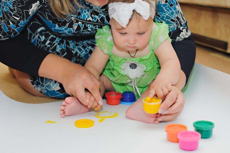 Behandla som ett barn lite målarfärg vid hennes händer på ett hem med modern arkivfoton