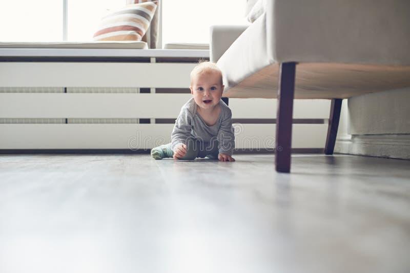 Behandla som ett barn lite pojkekrypningen på golv hemma fotografering för bildbyråer