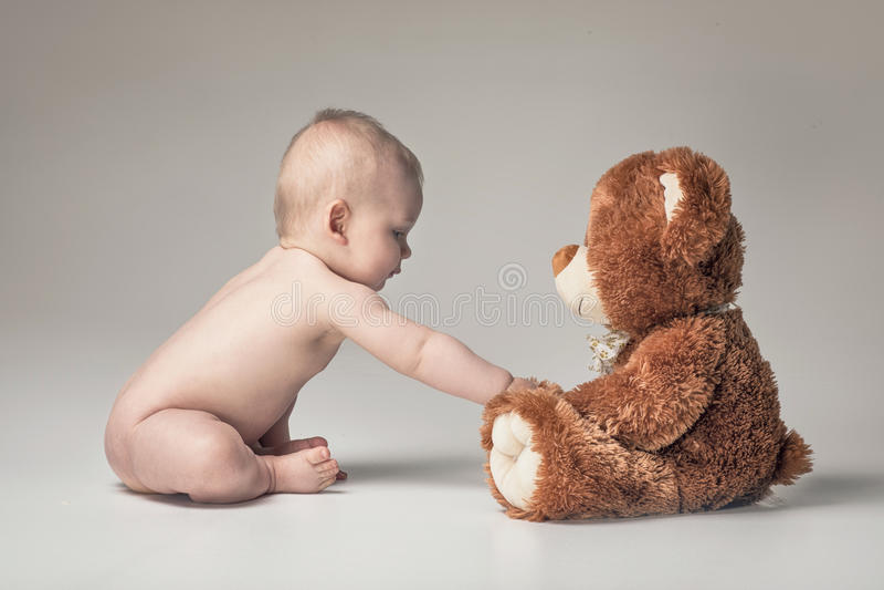 Behandla som ett barn lite pojken med nallebjörnen arkivfoto