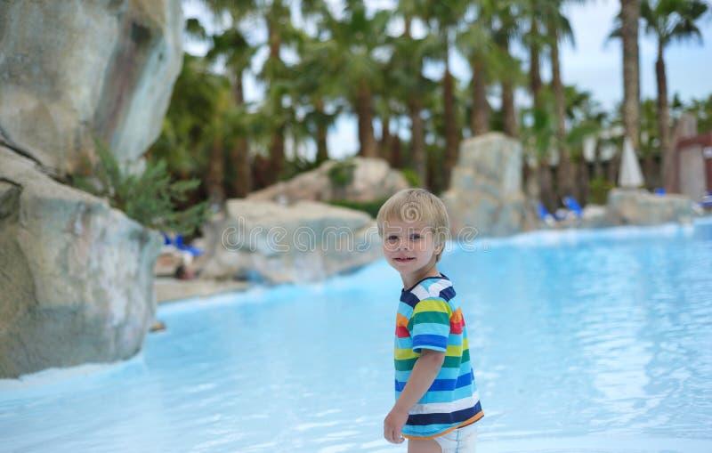 Behandla som ett barn lite pojken nära simbassäng fotografering för bildbyråer