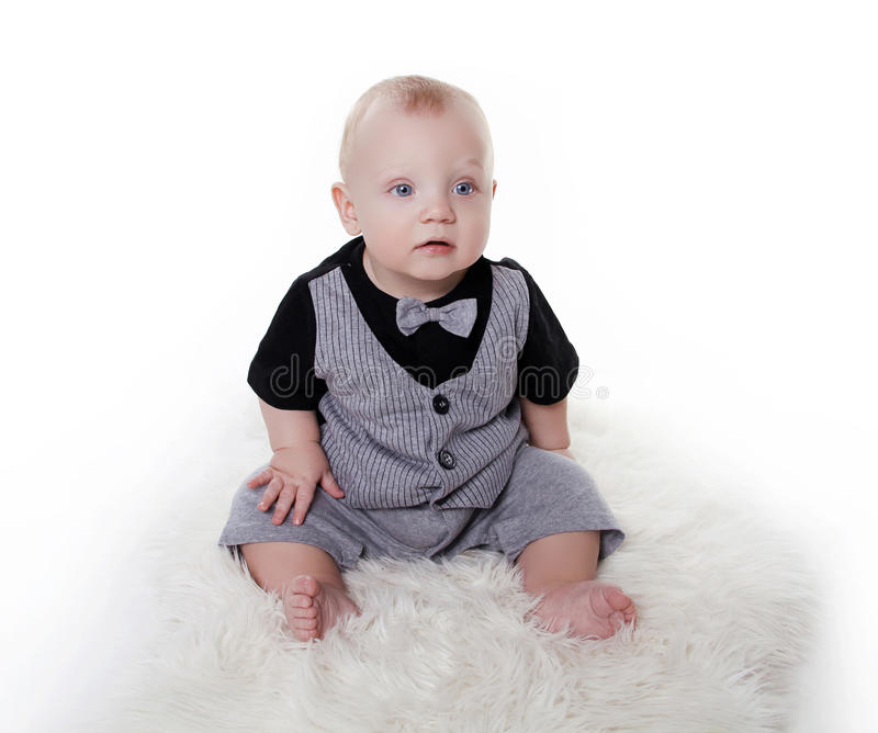Behandla som ett barn lite pojken som ha på sig i gentleman, passar över vitbac fotografering för bildbyråer