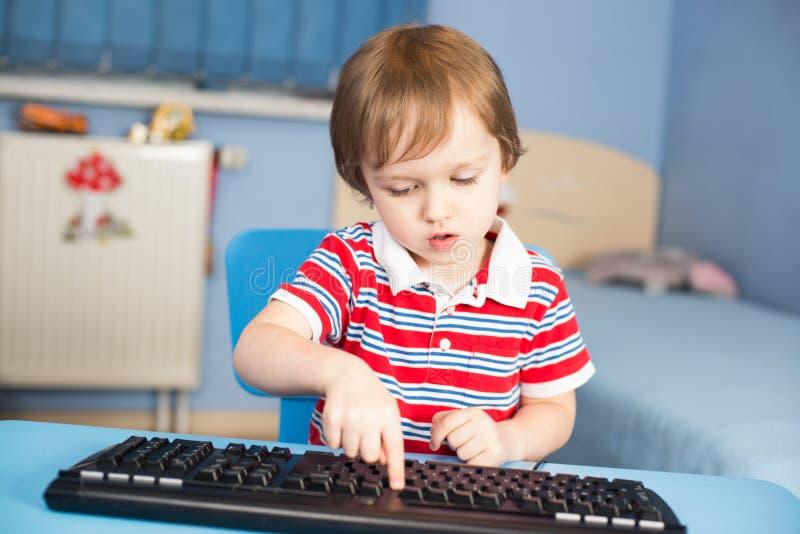 Behandla som ett barn lite pojken som maskinskrivning på datoren skrivar arkivfoto