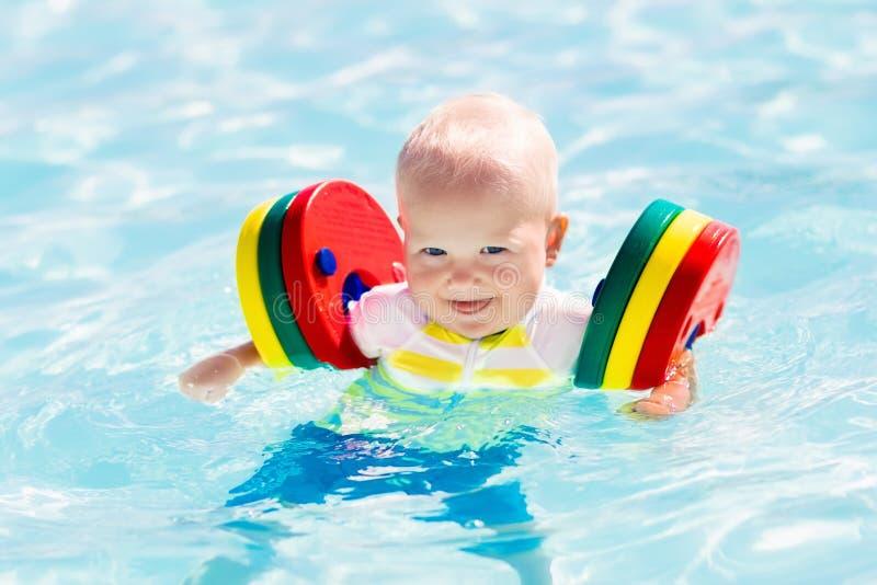 Behandla som ett barn lite pojken som spelar i simbassäng royaltyfri fotografi