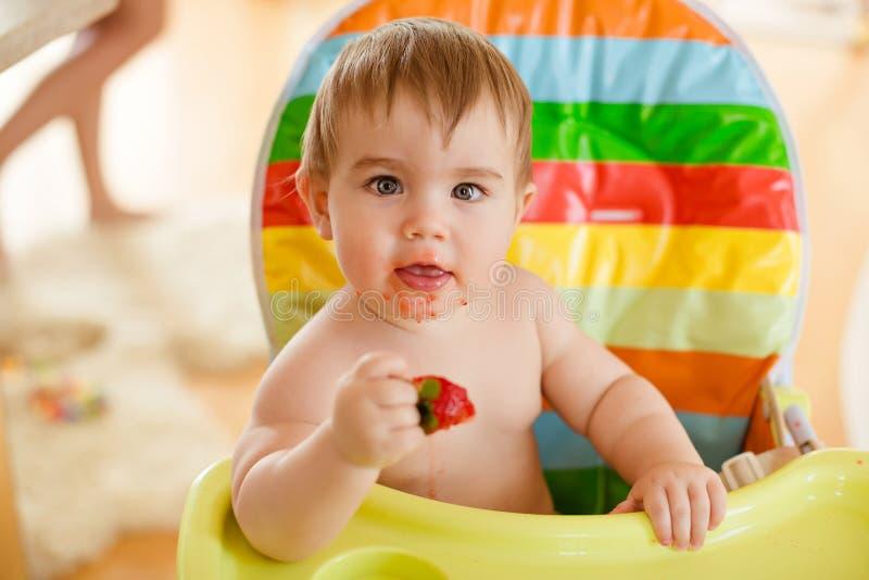 Behandla som ett barn lite pojkesammanträde i en ljus stol som äter jordgubbar royaltyfria foton