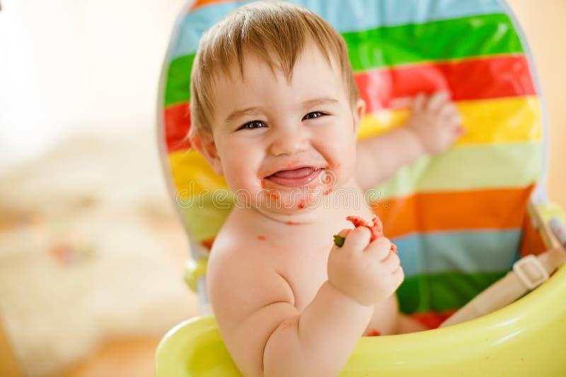 Behandla som ett barn lite pojkesammanträde i en ljus stol som äter jordgubbar a arkivfoton