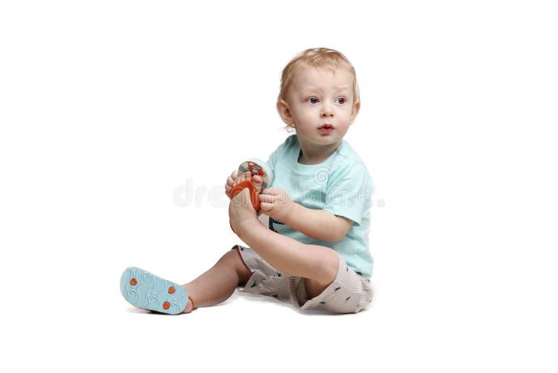 Behandla som ett barn lite pojkesammanträde på golvet, och innehavet som hans ben isolerade över vit fotografering för bildbyråer