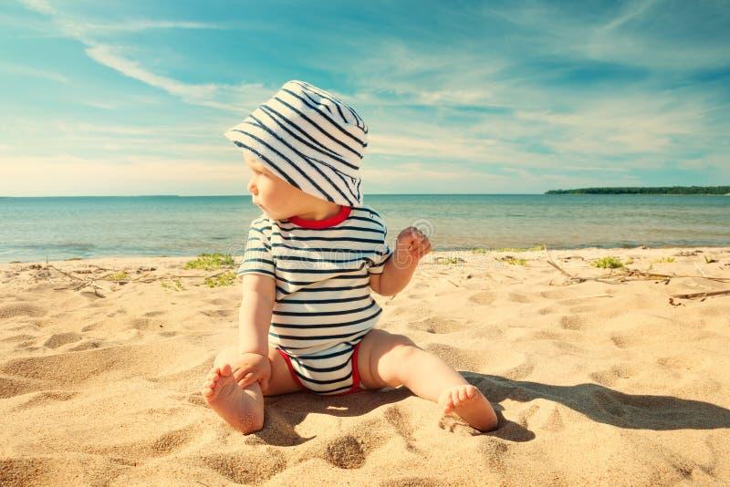Behandla som ett barn lite pojkesammanträde på stranden i sommardag arkivfoton