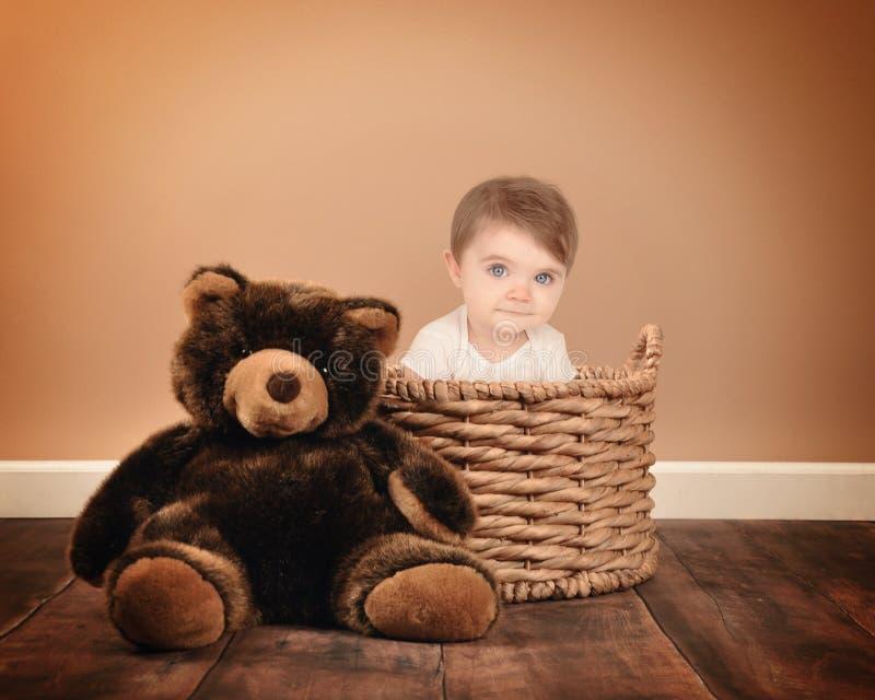 Behandla som ett barn lite sammanträde i korg med Teddy Bear arkivbilder