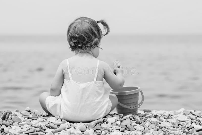 Behandla som ett barn lite sitter på ett Pebble Beach arkivfoto