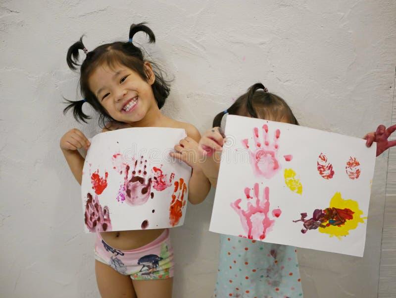 Behandla som ett barn liten asiat två flickor, systrar, tyckte om uppvisning deras konstverk, når han har gjort dem på egen ha arkivbilder