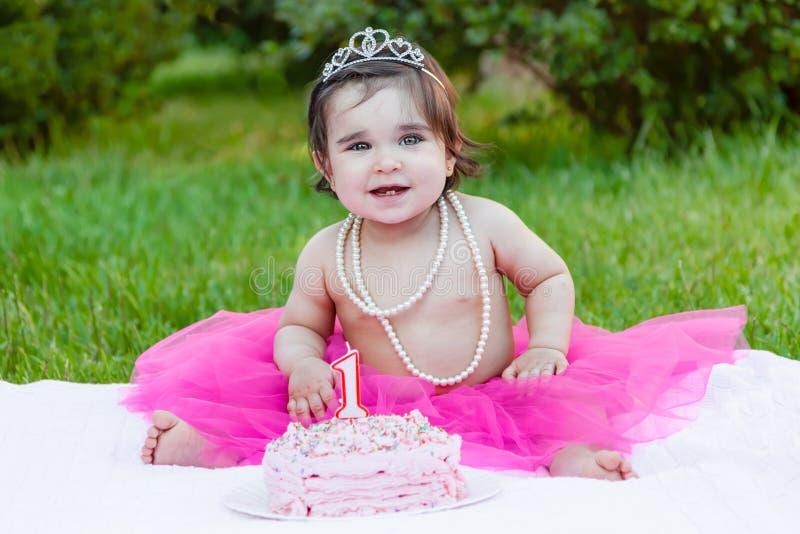 Behandla som ett barn litet barnflickan i det första födelsedagårsdagpartiet arkivbild