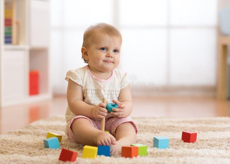 Behandla som ett barn litet barnflickan som spelar med träleksaker och har gyckel fotografering för bildbyråer