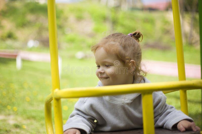 Behandla som ett barn lutat på gungan och värma sig ganska i solen fotografering för bildbyråer