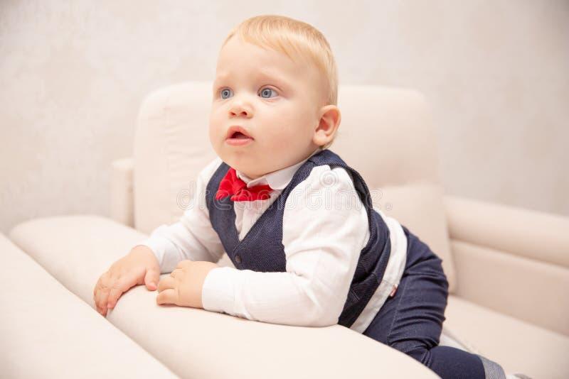 behandla som ett barn lyckligt Pys i en vit skjorta och fluga barn stänger upp flickaståenden Stilfull man i innegrej en fluga royaltyfria foton