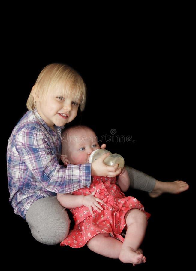 behandla som ett barn matande flickasysterbarn royaltyfria bilder