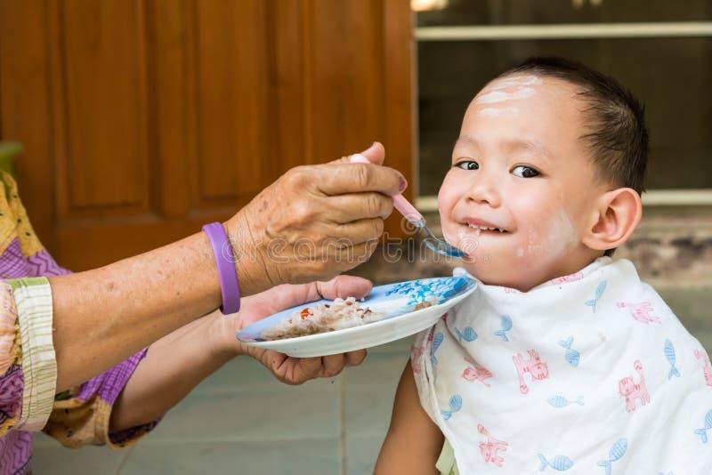 Behandla som ett barn matande mat för farmodern till thailändskt pojken royaltyfria foton