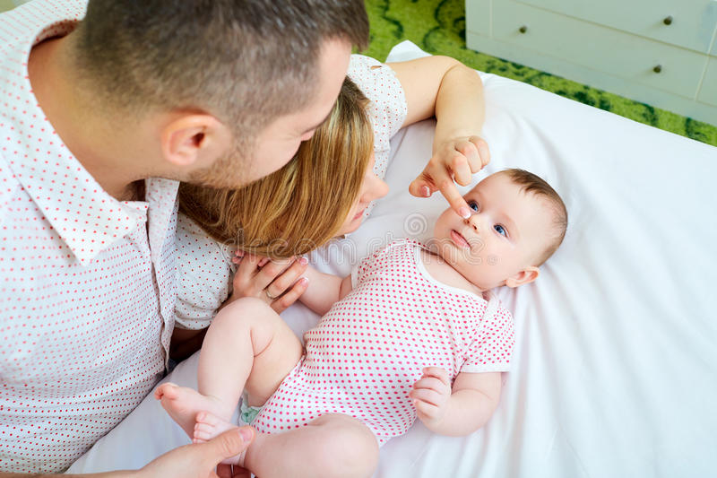 Behandla som ett barn med hans moder och fader på sängen som tillsammans spelar slump royaltyfri foto