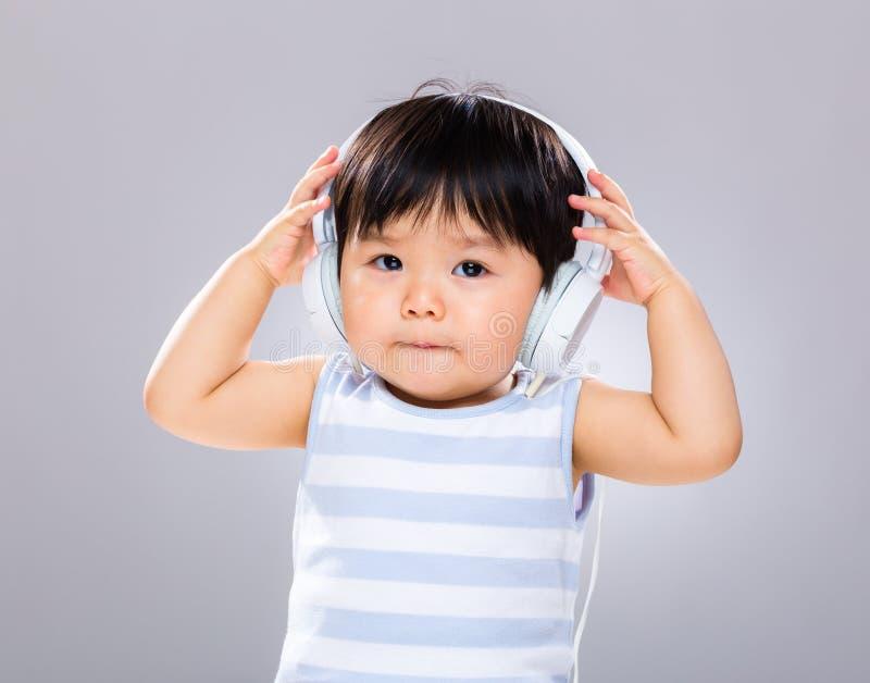 Behandla som ett barn med headphonen royaltyfri bild