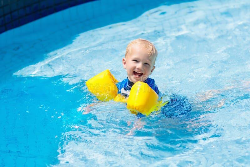 Behandla som ett barn med uppblåsbara armbindlar i simbassäng royaltyfria foton