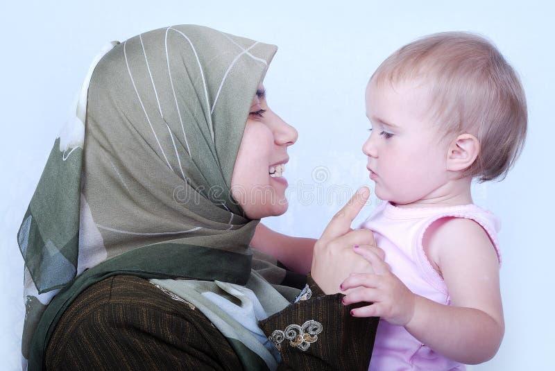behandla som ett barn modermuslim royaltyfri foto