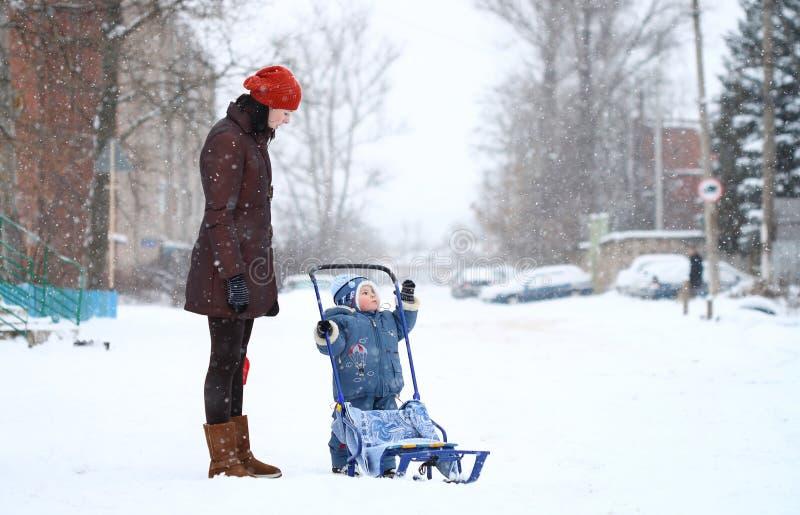 behandla som ett barn modern som pulkor går vinter arkivfoto