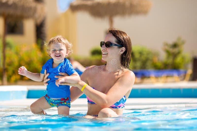 behandla som ett barn moderp?lsimning F?r?ldern och barnet simmar i en tropisk semesterort Utomhus- aktivitet f?r sommar f?r fami arkivfoton