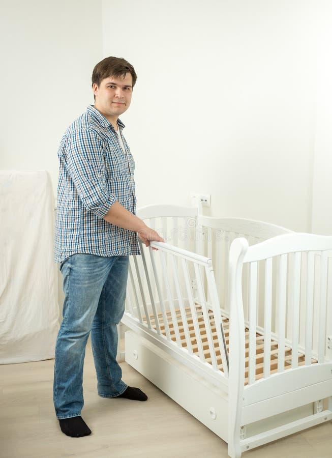 Behandla som ett barn monterande säng för den förväntansfulla fadern för hans framtid arkivfoto