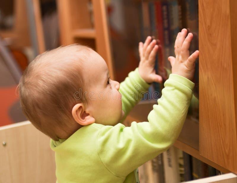 Behandla som ett barn nära bokhyllan royaltyfri fotografi