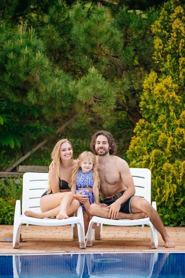 Behandla som ett barn och föräldrar som kopplar av på sunbed nära pöl på semesterorten Dana flickor, par, familj på semesterorten arkivfoton