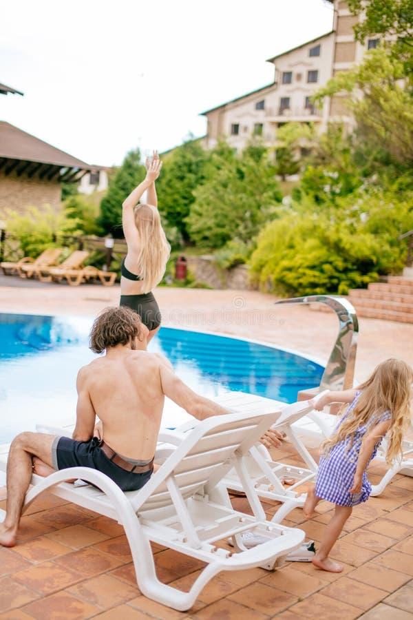 Behandla som ett barn och föräldrar som kopplar av på sunbed nära pöl på semesterorten Dana flickor, par, familj på semesterorten fotografering för bildbyråer