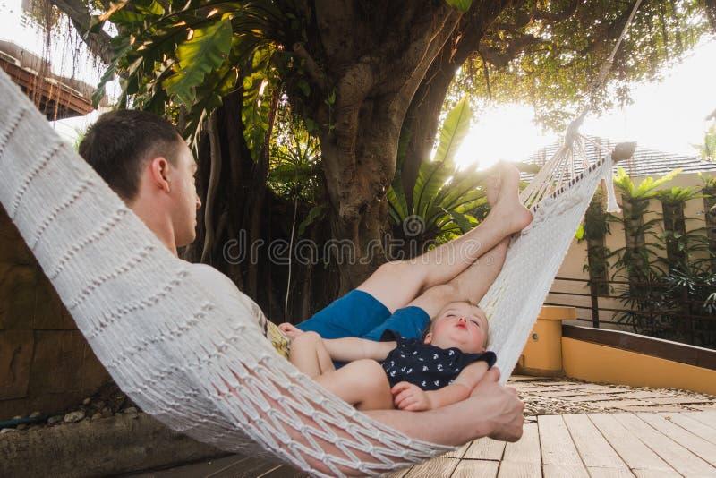Behandla som ett barn, och fadern sover i en hängmatta royaltyfria foton