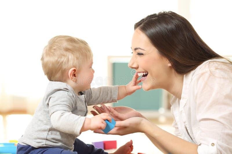 Behandla som ett barn och fostra att spela tillsammans på golvet arkivbild