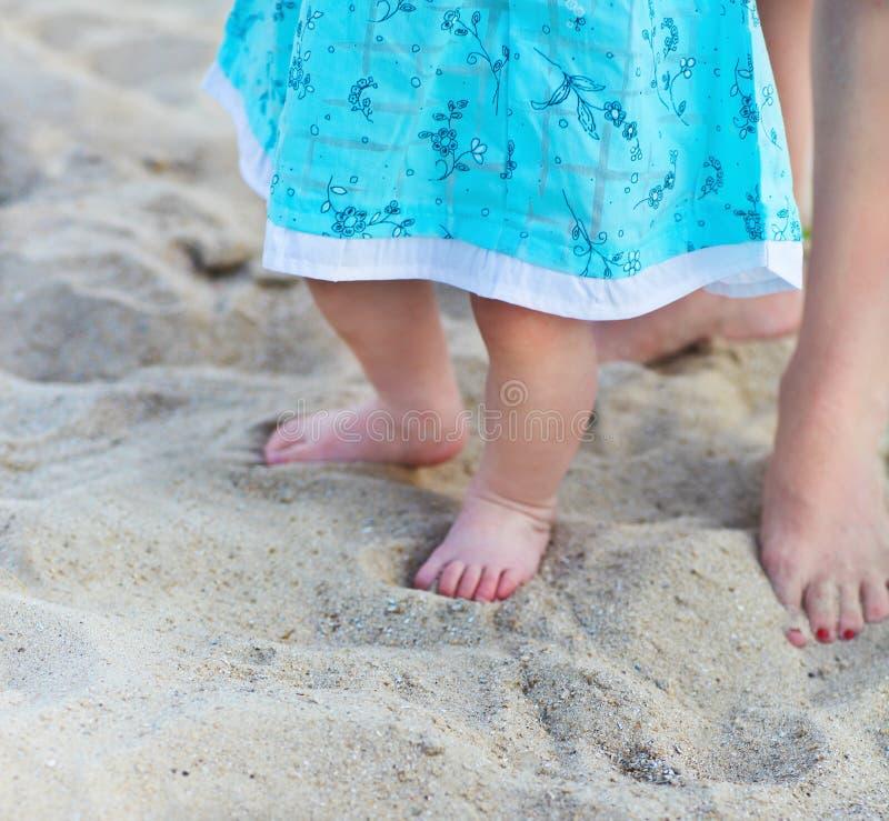 Behandla som ett barn och moderns fot på stranden arkivfoto