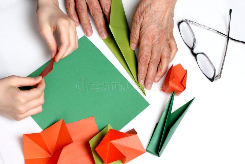 Behandla som ett barn, och mormodern gör origami royaltyfria bilder