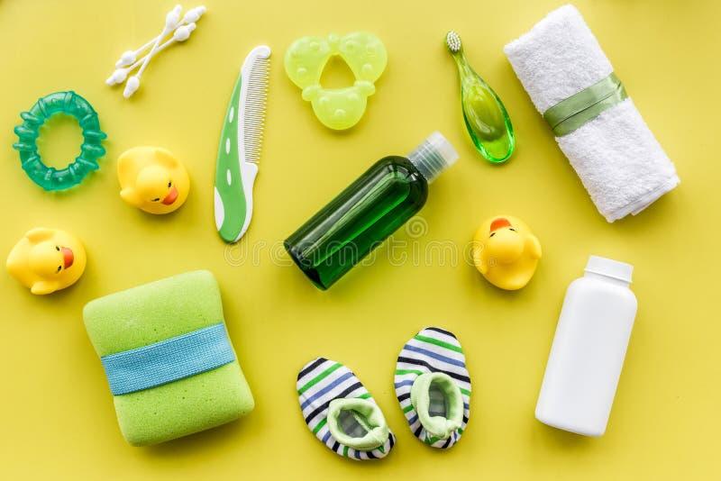 Behandla som ett barn omsorg med den baduppsättningen, ankungar och handduken på gul modell för bästa sikt för bakgrund royaltyfri bild