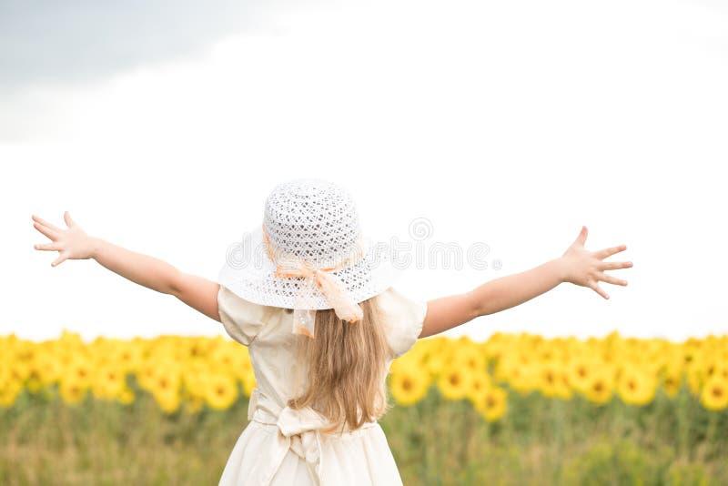 Behandla som ett barn på går i ett fält med i-blommor arkivbild
