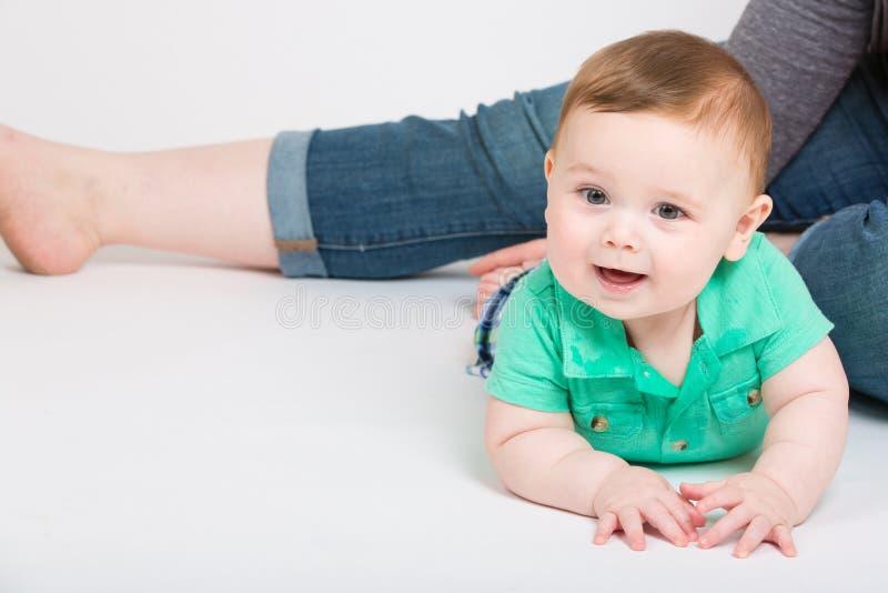Behandla som ett barn på magen med mamman i bakgrund royaltyfria bilder
